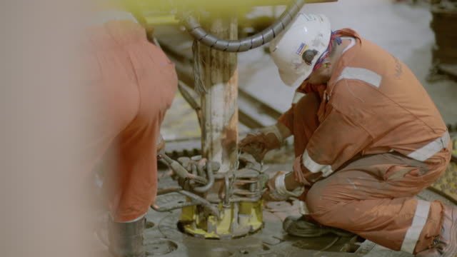 cu slo mo shot of roughnecks preparing large drill on oil rig / the north sea - industria petrolifera video stock e b–roll