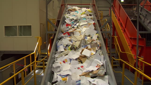 vídeos de stock, filmes e b-roll de ms shot of rubbish moving along conveyor belt into sorting machine to be recycled / london, united kingdom  - reciclagem