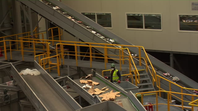 ms t/l shot of rubbish picker at work as rubbish moves past on conveyor belts in recycling centre / london, united kingdom  - リサイクル工場点の映像素材/bロール