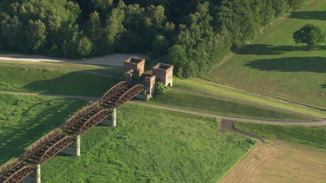 ms aerial zo shot of ruin railway bridge with river and farm field at domitz / germany - railway bridge stock videos & royalty-free footage