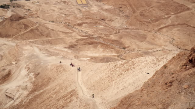 ws td shot of ruins and people walking up snake path of masada in negev desert / israel - religiöse darstellung stock-videos und b-roll-filmmaterial