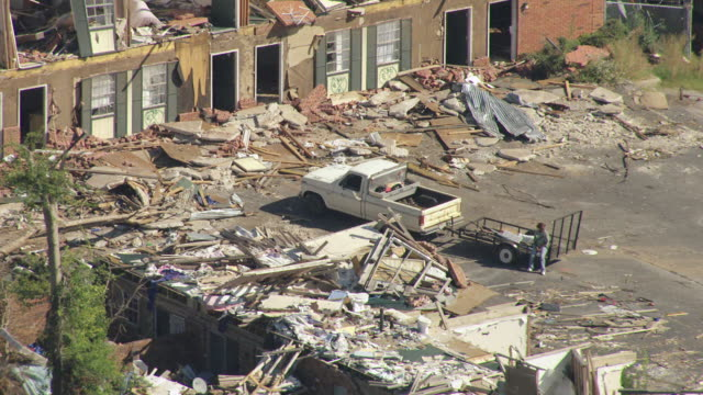 ms aerial zo shot of ruins of tornado damaged homes and person sitting on back of truck / tuscaloosa, alabama, united states - 荒廃した点の映像素材/bロール