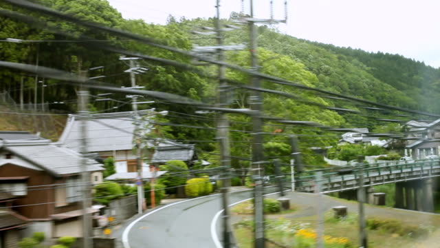 ms pov shot of rural area with small towns and rice fields seeing from window of passing train / kyoto, kanto, japan - ワイヤー点の映像素材/bロール