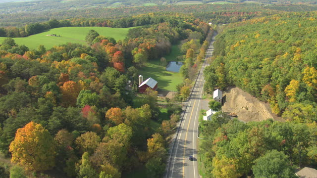 ms aerial ts shot of rural highway with cars driving past farms in bedford county / pennsylvania, united states - ペンシルベニア州点の映像素材/bロール