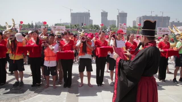 vídeos y material grabado en eventos de stock de ms shot of sacrificial ceremony before traditional dragon boat race during dragon boat festival / xian, shaanxi, china  - accesorio de cabeza