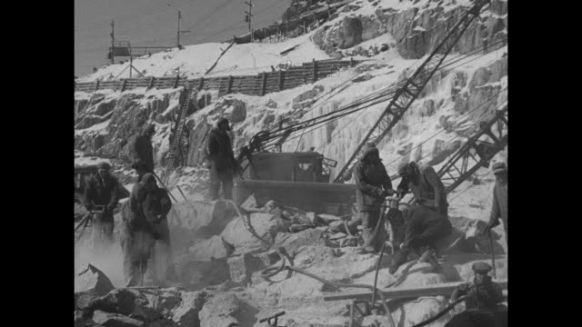 Shot of Saguenay River in snowy landscape / three shots of men working on partially completed dam / VS men drilling / two shots of dynamite...