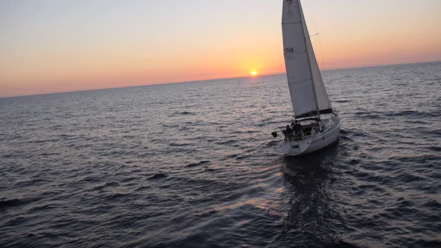 MS AERIAL POV SLO MO Shot of Sailboat from behind and sweeping past as sailboat sails into sunset on ocean / Newport Beach, California, United States
