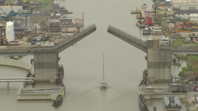 ms aerial zo shot of sailboat under small drawbridge / louisiana, united states - drawbridge stock videos and b-roll footage