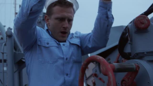 MS Shot of sailor gets into position and starts maneuvering gun mount on battleship deck / Evansville, Indiana, United States