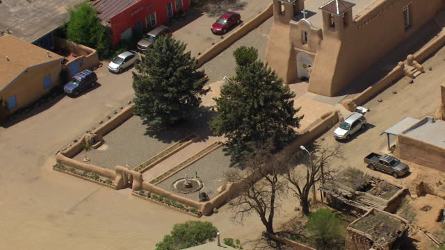 stockvideo's en b-roll-footage met ms aerial zi shot of san francisco de asis mission church and tight on steeples and visitors entering church / new mexico, united states - plaatselijk monument