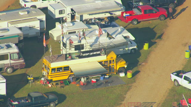 ms aerial shot of school bus at tailgating at talladega superspeedway / lincoln, alabama, united states - camper trailer stock videos and b-roll footage