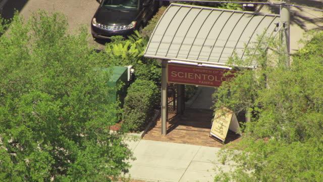 vidéos et rushes de ms aerial shot of scientology sign in between trees / tampa, florida, united states - panneau d'entrée