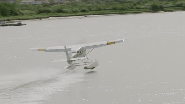 MS AERIAL TS Shot of sea plane taking flight off Naknek river / Alaska, United States