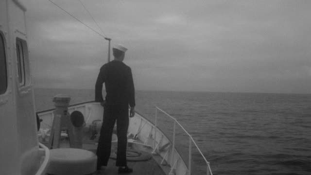 MS Shot of seaman on bow of coast guard looking out to ocean