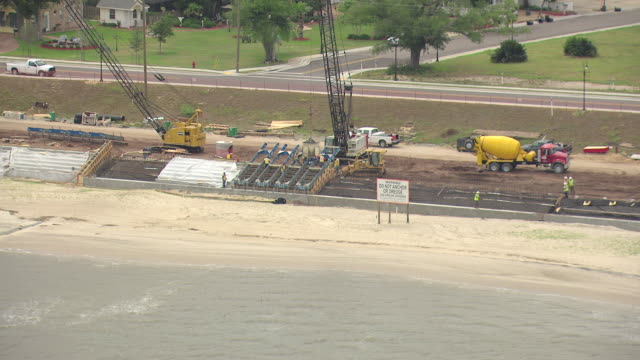 MS AERIAL ZO Shot of seawall construction site and sea water with beach and community buildings on land / Waveland, Mississippi, United States