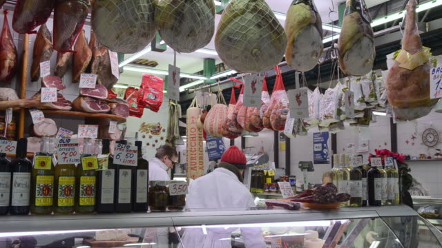 vídeos de stock, filmes e b-roll de ms shot of seller in butcher shop with delicatessen in ambrogio market / florence, tuscany, italy - loja de conveniência
