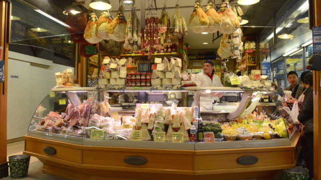 ms shot of seller in delicatessen shop with salami, cheese and ham in ambrogio market / florence, tuscany, italy - markthändler stock-videos und b-roll-filmmaterial