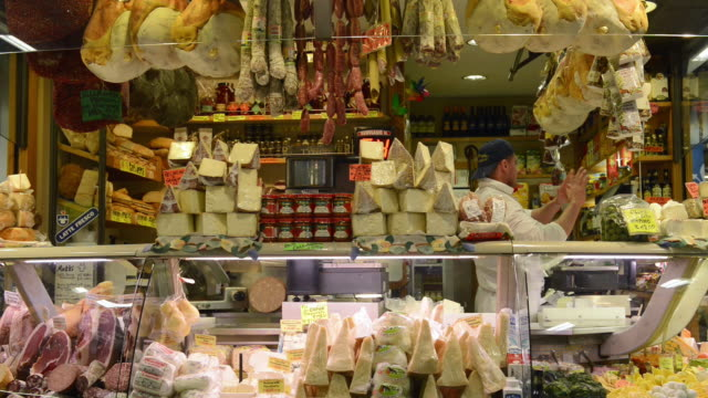 ms shot of seller in delicatessen shop with salami, cheese and ham in ambrogio market / florence, tuscany, italy - デリカッセン点の映像素材/bロール