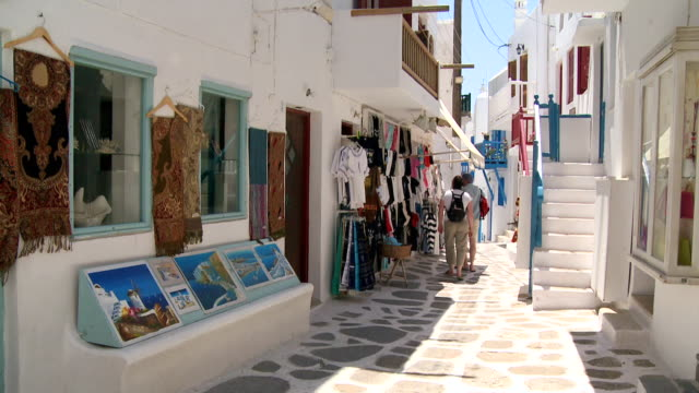 ms shot of selling of clothes on small alley of city / mykonos, cyclades, greece - mykonos stock videos and b-roll footage