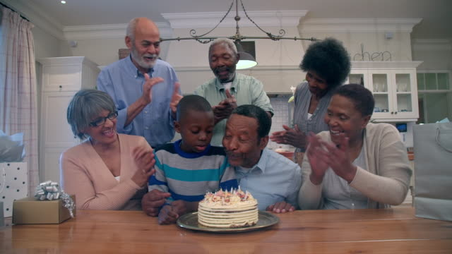 vidéos et rushes de ms zi shot of senior african and mixed race friends with grandchild celebrating a birthday / cape town, western cape, south africa - famille multi générations