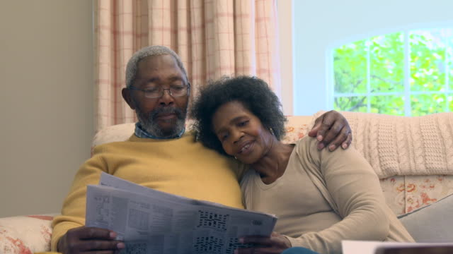vídeos de stock, filmes e b-roll de ms shot of senior african  couple sitting on sofa reading newspaper / cape town, western cape, south africa - óculos de leitura