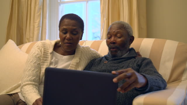MS PAN Shot of senior African couple sitting on sofa using laptop / Cape Town, Western Cape, South Africa