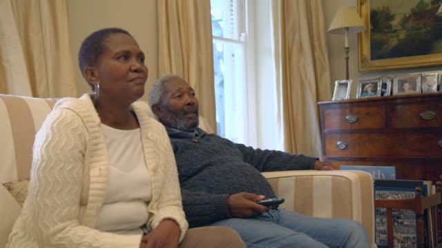 ms shot of senior african couple sitting on sofa watching television / cape town, western cape, south africa - guardare la tv video stock e b–roll