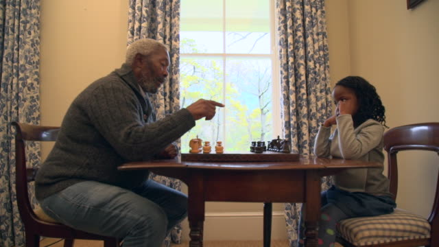 ms pan shot of senior african man playing chess with grandchild / cape town, western cape, south africa - board game stock videos & royalty-free footage