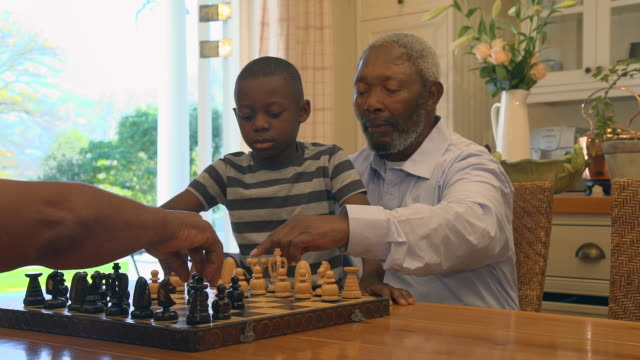 ms pan shot of senior african man teaching grandchild to play chess / cape town, western cape, south africa - grandchild stock videos & royalty-free footage