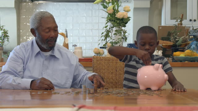 ms shot of senior african man with grandchild putting coins into piggy bank / cape town, western cape, south africa - piggy bank stock videos & royalty-free footage