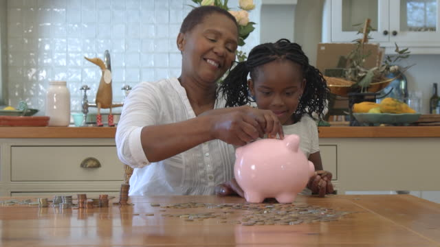 ms zi zo shot of senior african woman sitting with grandchild and putting coins into piggy bank / cape town, western cape, south africa - savings stock videos & royalty-free footage