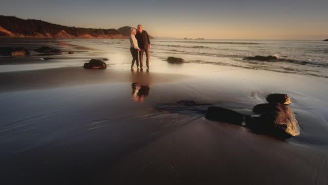 ms shot of senior couple walking on beach at sunset / port orford, oregon, united states  - senior couple stock videos & royalty-free footage