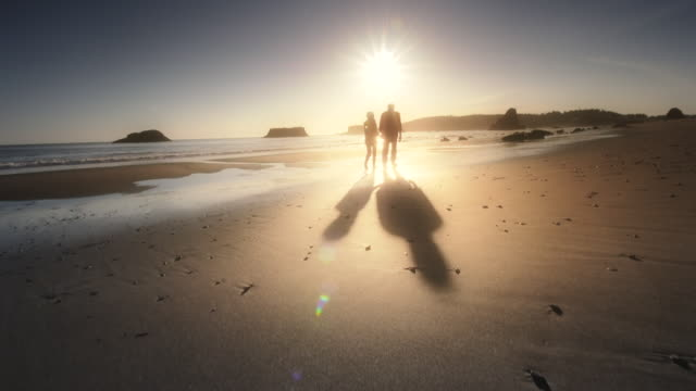 ms pov shot of senior couple walking on beach at sunset / port orford, oregon, united states  - pensionierung stock-videos und b-roll-filmmaterial