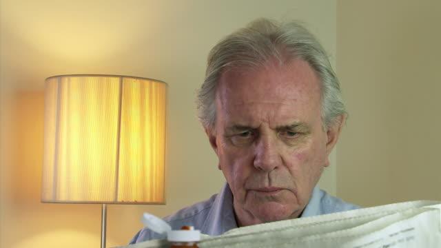 MS Shot of senior male reads newspaper at breakfast / Estepona,Espana, Malaga, Spain