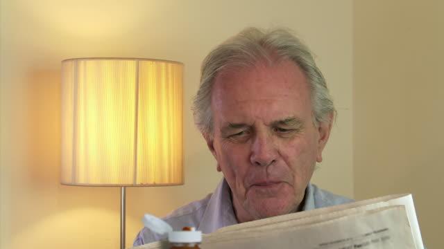 MS Shot of senior male reads newspaper at breakfast laughing / Estepona,Espana, Malaga, Spain