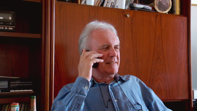 ms shot of senior male talking on phone / spain - solo un uomo anziano video stock e b–roll