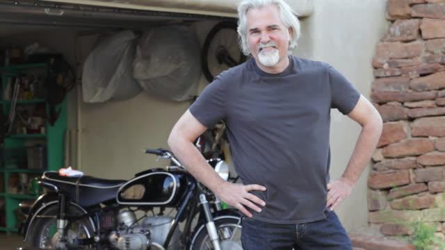 vidéos et rushes de cu tu shot of senior man and his motorcycle / santa fe, new mexico, united states - portrait image