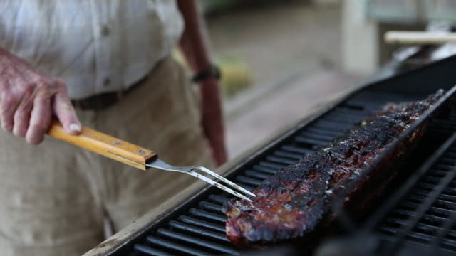 CU TU Shot of senior man cooking ribs on outdoor grill / Lamy, New Mexico, United States