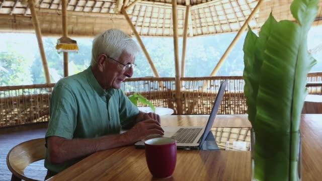ms shot of senior man using his laptop / ubud, bali, indonesia - ワーキングシニア点の映像素材/bロール