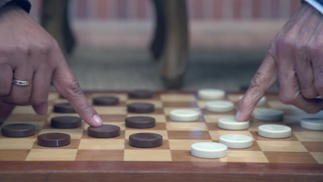 cu pan shot of senior mixed race  couple playing checkers by fireside / cape town, western cape, south africa - draughts stock videos & royalty-free footage