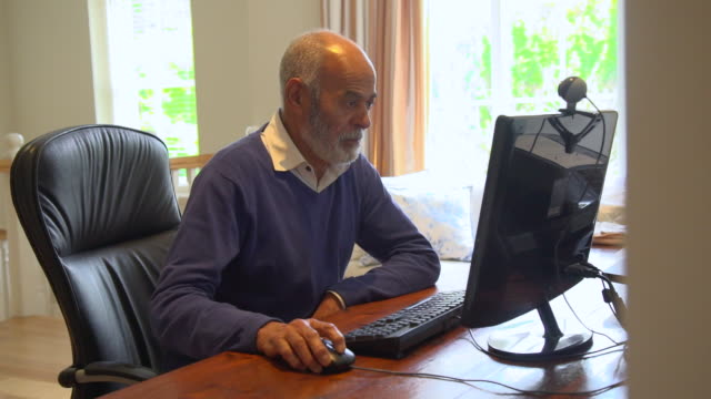 vídeos de stock, filmes e b-roll de ms shot of senior mixed race man using personal computer / cape town, western cape, south africa - homens idosos