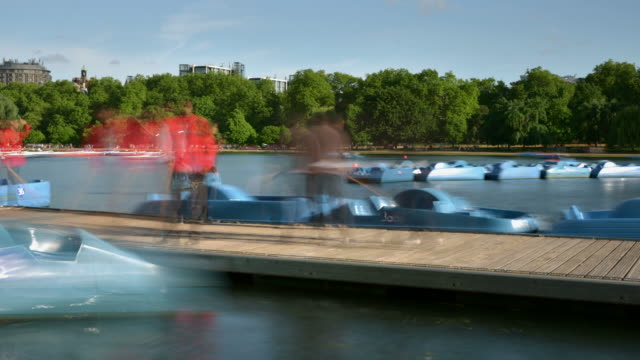 ms pan t/l shot of serpentine hyde park and boat jetty with pedal boats moving in and out and tourists enjoying summer day in water / london, greater london, united kingdom - pedal boat stock videos and b-roll footage