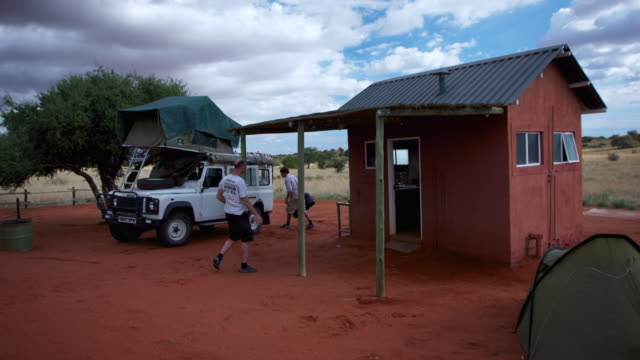 vídeos y material grabado en eventos de stock de ms t/l shot of setting up camp with atv beside ablution hut on intensely red earth surrounding by pale savannah and blue sky with scudding white clouds / kalahari, windhoek, namibia - 4x4