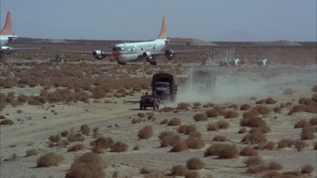 vídeos de stock, filmes e b-roll de ws ts shot of several army jeeps and trucks drive in desert near airplanes  - carro blindado