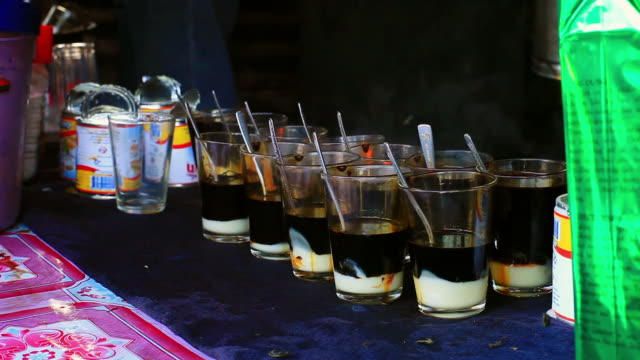 ms shot of several glasses lined up with condensed milk and hot water for making coffer / luang prabang, laos - condensed milk stock videos & royalty-free footage