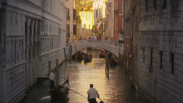 Shot of several gondolas in a canal with a bridge.