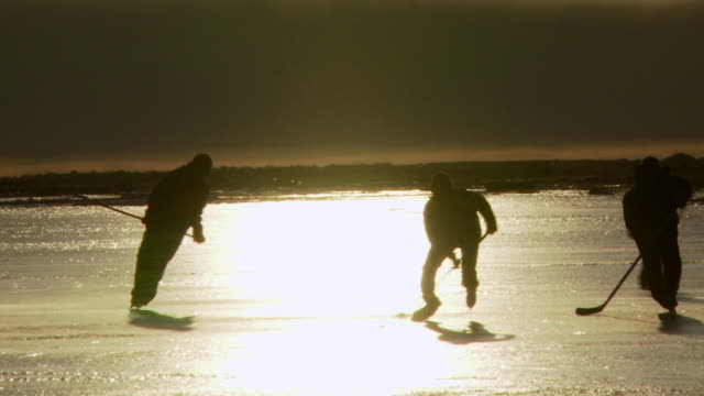 ms shot of several hockey players with stick handles skating on ice / arviat, nunavut, canada - wiese stock videos & royalty-free footage