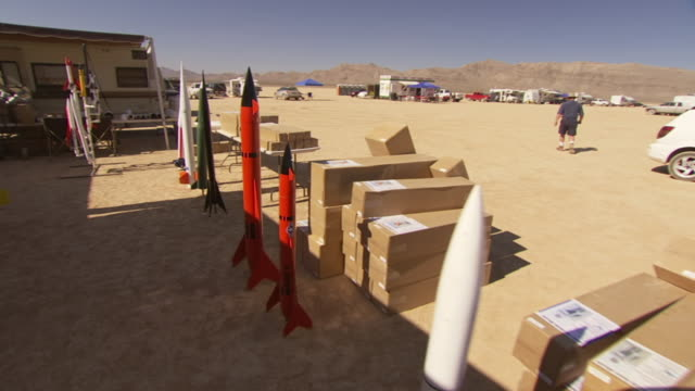 MS TS shot of several rockets stand near trailer before BALLS Experimental Rocket Launch desert / Black Rock, Nevada, United States