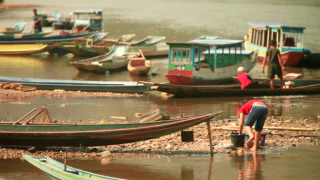 ms shot of several small wooden boats mooring and girl washing clothes near river / mountain village near muang ngoi, luang prabang, laos - floating on water stock videos & royalty-free footage