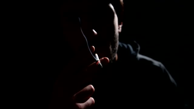 CU Shot of shadowed young man smoking in silhouette / Rome, Lazio, Italy